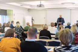 Person står och talar inför andra under mötet