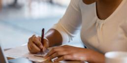 Person för anteckningar på papper vid bärbar dator
